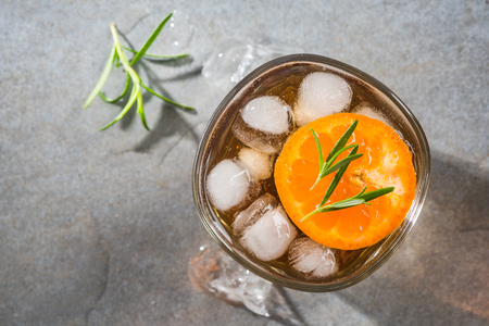 Glass with ice cold tea beverage and rosemary garnish. Stock Photo