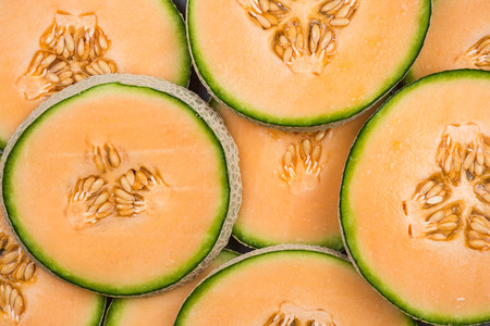 Cantaloupe melon slices, full frame food background.