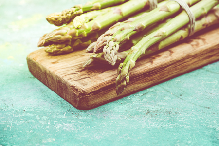 Green asparagus close up on wooden board