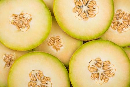 Honeydew green melon slices, food background. Full frame, close up.