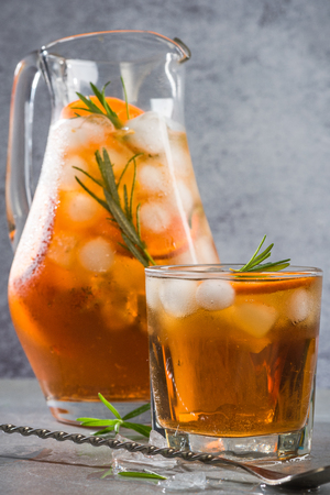 Ice cold tea in pitcher and glass with rosemary garnish.