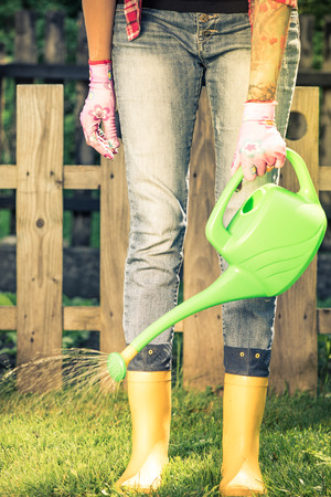 Tattooed woman watering plants in garden wearing wellies. Foto de archivo - 102622898