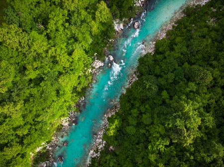 Emerald green Soca river in Slovenia, top down aerial photo.