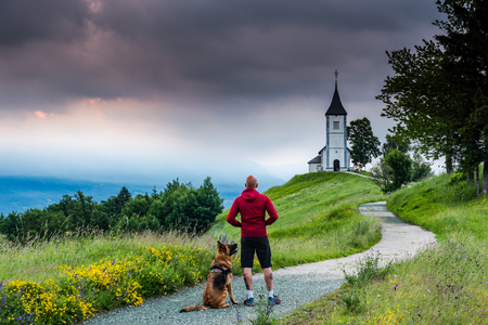 Man with dog looking at  Church of  St. Primus and Felician, Jamnik, Slovenia