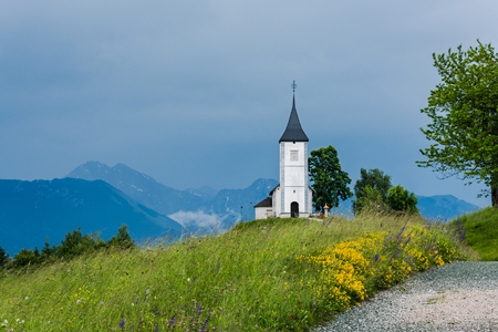 Church of St. Primus and Felician, Jamnik Slovenia at stormy weather. Stock Photo