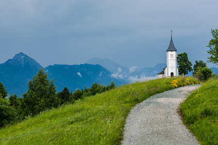 Church of St. Primus and Felician, Jamnik Slovenia at stormy weather. Stock Photo - 102745430