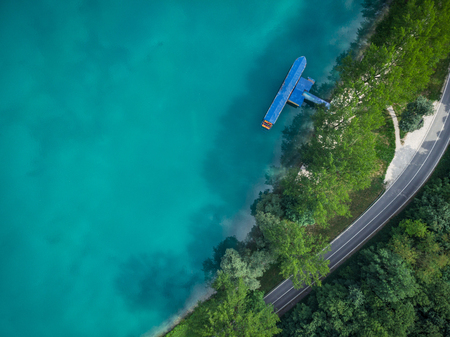 Top down aerial view over Most na Soci,Slovenia. Half water with road and forest.