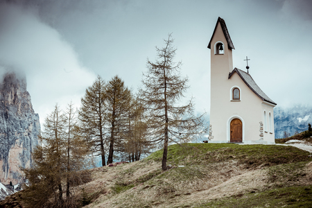 Lonely Chapel on cloudy day in South Tyrol,Italy. Rocks in background. Gardena Pass,Italy. Stock Photo