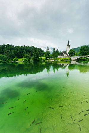 Cristal clear water and Church of Sv. John the Baptist  by the Bohinj lake, Slovenia