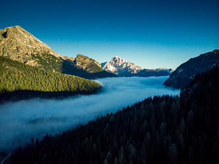 Morning fog over forest in Italian Dolomites mountains, aerial drone view. Stock Photo