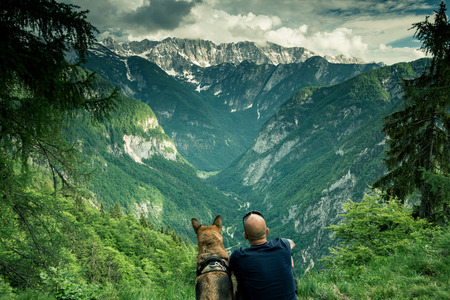 Man with dog looking at view in triglav Park, Julian Alps, Slovenia.