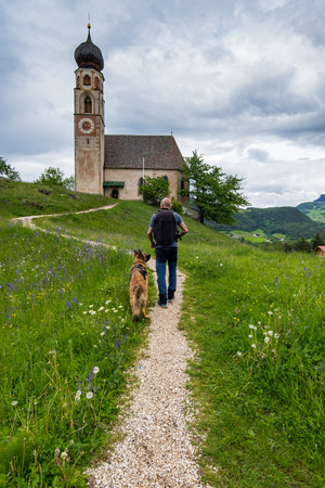 Man walking with dog to see St. Konstantin, Voels, Church in Alpe di Siusi, Italy