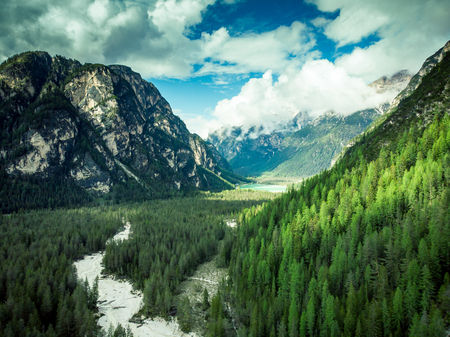 Amazing view over Dolomites peaks, forest and river,Italy, aerial drone view. Stock Photo