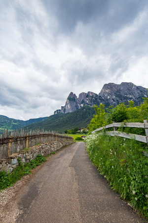 Empty road leading into Alpine mountains. Alpe di Siusi, Dolomites. Italy Stock Photo