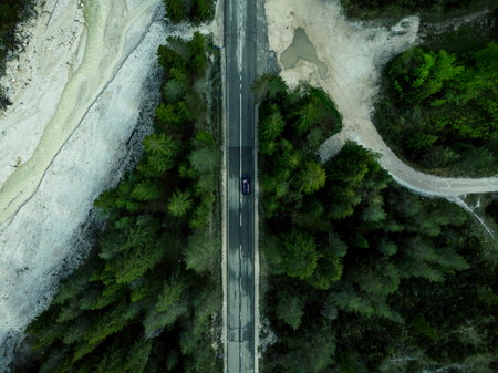 Car driving on alpine road in forest, top down aerial drone view.