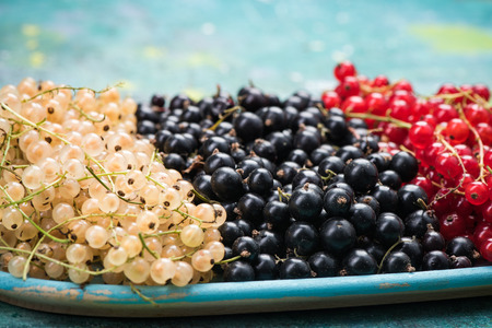 White currant, redcurrant and blackcurrant, on wooden plate. Stok Fotoğraf