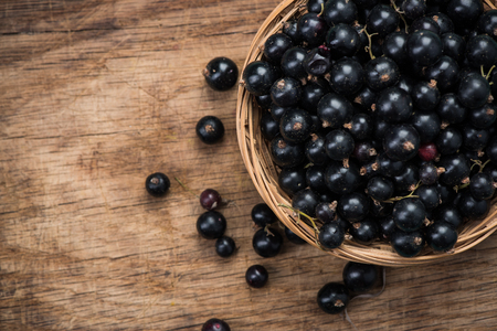 Fresh ripe blackcurrant in basket, copy space on wooden board.