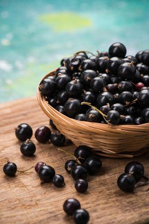 Fresh ripe blackcurrant in basket, copy space on wooden board.