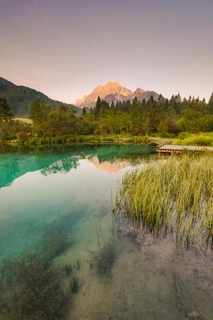 Beautiful sunrise over emerald green water in Zelenci spring. Standard-Bild - 104543941