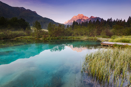 Beautiful sunrise over emerald green water in Zelenci spring.