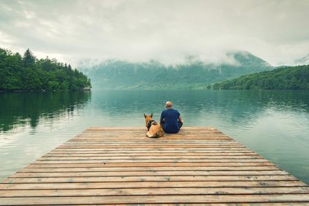 Man with dog sitting at wooden pier at Bohinj Lake, SLovenia.