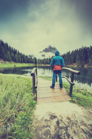Active man standing at Atorno Lake at Tre Cime di Lavaredo, Italy Standard-Bild - 105622394