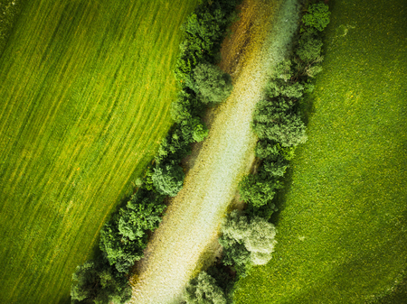 Top down aerial drone view on river and pasture fields Imagens