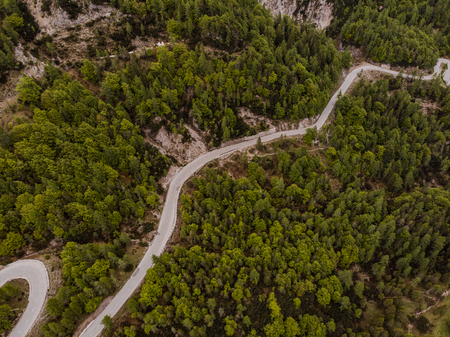 Alpine road in forest , aerial drone view Banco de Imagens