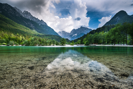 Clear water and Julian Alps reflection in Lake Jasna, Slovenia. 스톡 콘텐츠