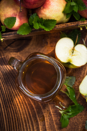 Freshly made apple juice on wooden table Imagens