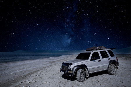 Off road car on beach under MIlky Way night sky Stock Photo