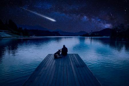 Mężczyzna z psem patrząc na deszcz meteorytów Perseidów nad jeziorem Bled