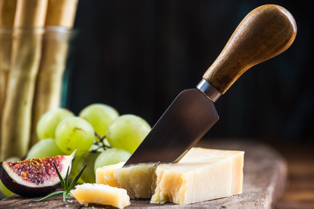 Parmesan cheese pieces cut by cheese knife.