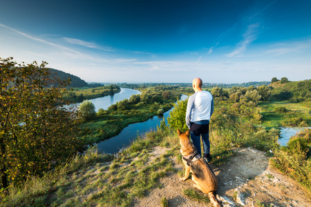 Active man and dog looking at Vistula river,Poland.