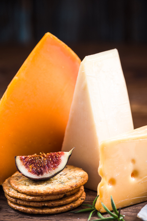 Cheese served with crackers and fig.