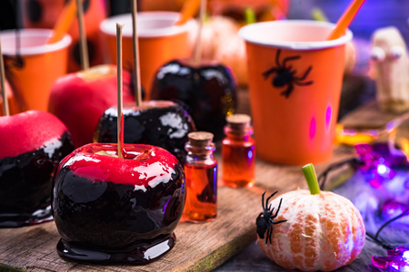 Sweet red candy apples on Halloween party table. Stock Photo