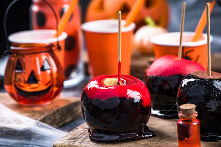 Glazed candy apples on Halloween party table.