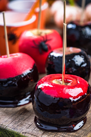 Candy apples on wooden board.