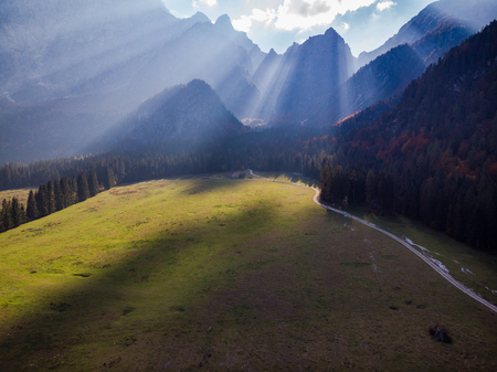 Dramatic sky with sun rays over alpine valley. Stock fotó