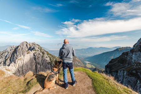 Man with dog looking at scenic view from high peak.