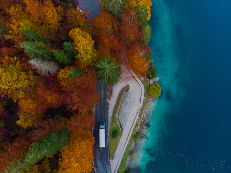 Car drive on road in autumn forest by lake, aerial view. Stock Photo