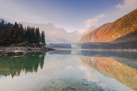 Mist at alpine lake with atumn colors in forest.