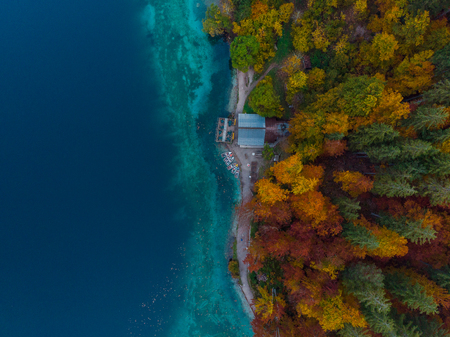 Colorful boats on lake by autumn forest , Fusine lake, aerial view.