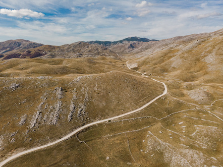 Rural road in unspoiled hills and steppe in Bosnia. Aerial drone view Banco de Imagens
