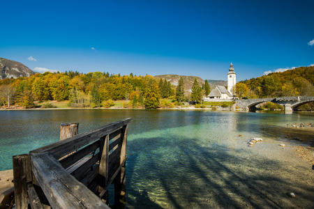 Gothic Church of St. John the Baptist and stone bridge in Ribcev Laz, lake Bohijn,Slovenia.