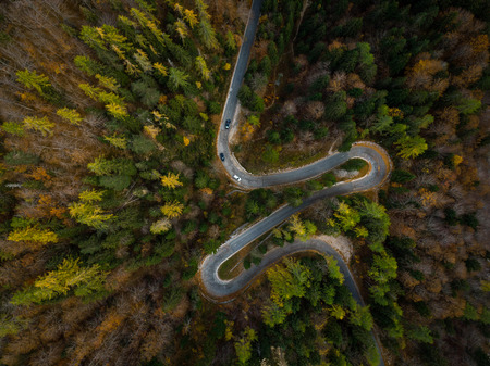 Winding road in mountains, fall woodlands, drone view from above. Stock Photo