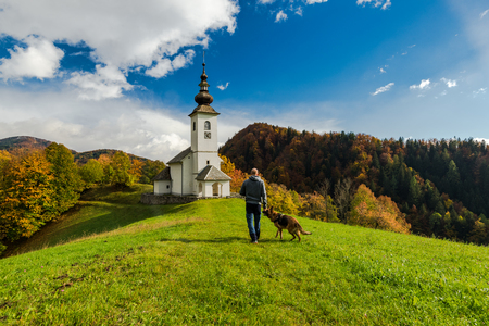 Man walking toward rural church in Slovenia with his dog. Stock Photo