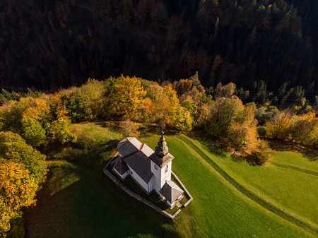 Aerial view of rural church or chapel in Slovenia at autumn.