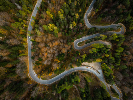 Winding road in mountains, fall woodlands, drone view from above. Фото со стока