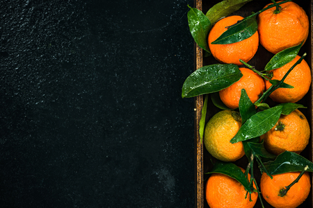 Tangerines or clementines in wooden crate, border background.